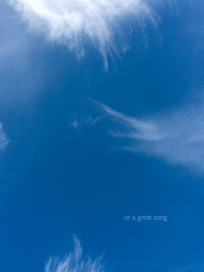 "A photograph of whispy clouds in a blue sky with the words ""or a great song"""